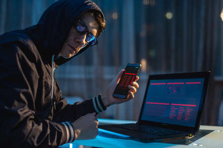 Male hacker in the hood holding the phone in his hands trying to steal access databases with passwords. The concept of cyber security