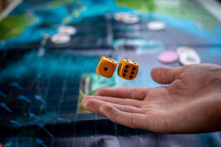 De hand gooit gele dobbelstenen op het speelveld. Geluk en opwinding. Het concept van bordspellen. Gamemomenten in dynamiek Stockfoto