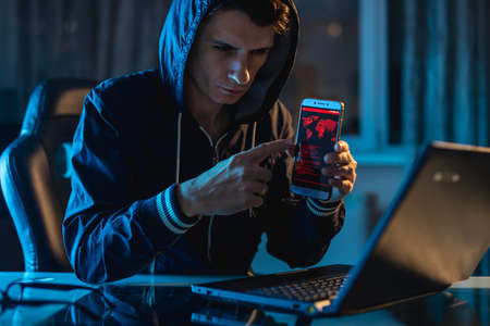 Hacker in the hood holding the phone in his hands trying to steal access databases with passwords. The concept of cyber security