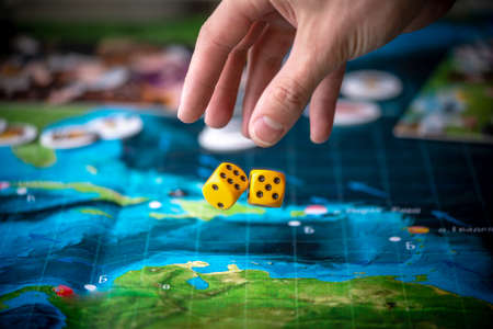 Hand throws two yellow dice on the playing field. Gaming moments in dynamics. Luck and excitement. Concept Board games strategy