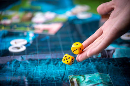 The hand throws two yellow dice on the blue field of the fantasy game. Gaming moments in dynamics. Luck and excitement. Concept Board games strategy