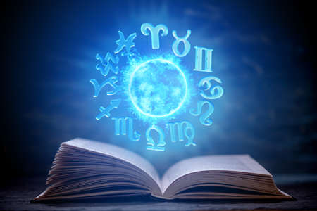 Open book on astrology on a dark background. The glowing magical globe with signs of the zodiac in the blue light. Prediction and magic