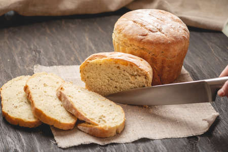 Womens hands cut with a knife homemade natural fresh bread with a Golden crust on a napkin on an old wooden background. The concept of baking bakery products Stock Photo