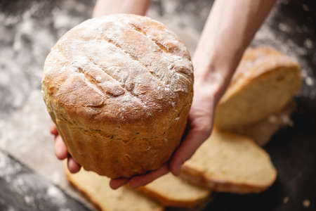 Female hands holding homemade natural fresh bread with a Golden crust on a napkin on an old wooden background . The concept of baking bakery products