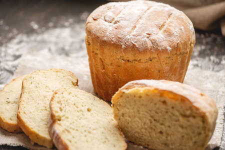 Homemade natural fresh bread with a Golden crust on a napkin on an old wooden background . The concept of baking bakery products