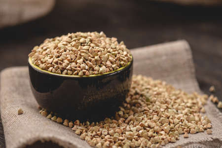 Croup green buckwheat on a dark background. Vegan nutritious and healthy product. Concept of organic food Stock Photo