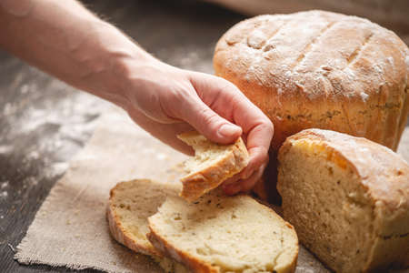 Womens hands breaking homemade natural fresh bread with a Golden crust on a napkin on an old wooden background. Concept of baking bakery products
