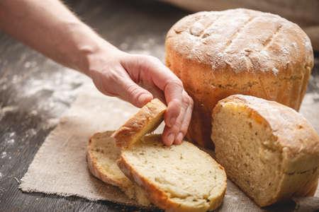 Le mani delle donne che rompono il pane fresco naturale fatto in casa con una crosta dorata su un tovagliolo su un vecchio sfondo di legno. Il concetto di cuocere prodotti da forno Archivio Fotografico