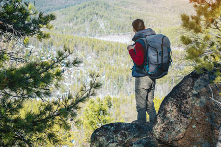 Man tourist hiker with a large backpack stands on a rock cliff and looks at the sprawling green valley. The concept of freedom in travel