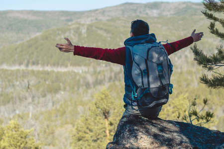 A male tourist hiker with a large backpack stands on a cliff stone in front of a green valley with his arms outstretched. The concept of freedom in travel Stock Photo