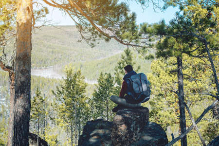 Man tourist hiker with a large backpack sitting on a rock cliff and looking at the sprawling green valley. The concept of freedom in travel