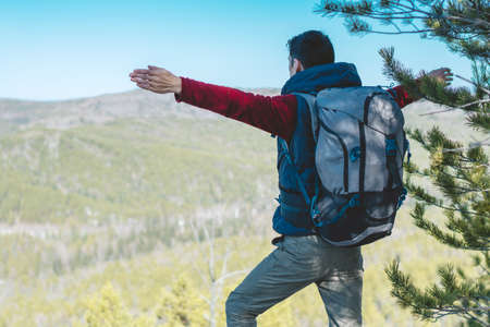 A male tourist hiker with a large backpack stands on a cliff stone in front of a green valley with his arms outstretched. The concept of freedom in travel Banque d'images