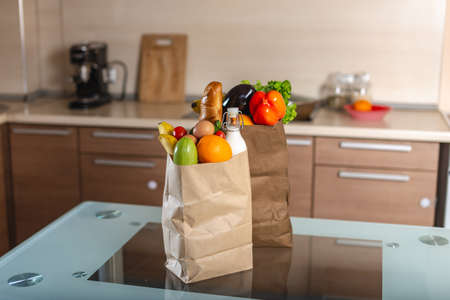 Full paper bags with foods on the table on the background of the kitchen. Healthy and fresh eco products for a balanced diet. Stock Photo