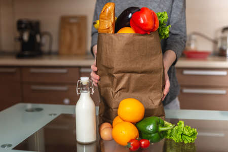 A woman unpacks a full paper bag with products on the background of the kitchen. Healthy and fresh organic food for a balanced diet.