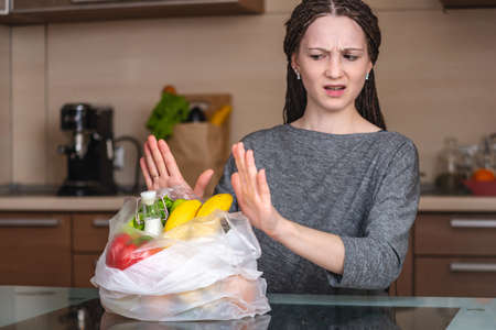 A woman thinks that would refuse to use a plastic bag to buy products in the store. The concept of environmental protection and the abandonment of plastic Standard-Bild