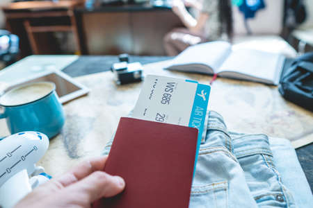 Hand holding a passport and two tickets on the background of the camera, the world map, the plane. The concept of preparing for the journey to meet adventures Imagens