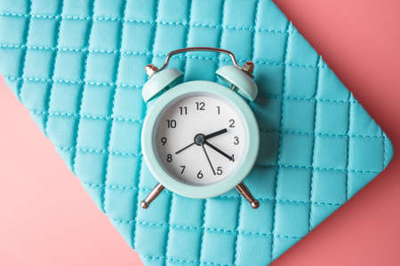 Blue analog metal alarm clock on stylish blue-pink background. The concept of time in pastel colors 版權商用圖片 - 121865460