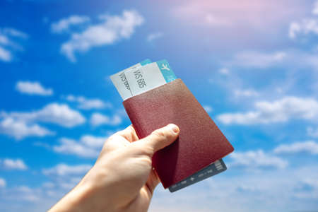 Hand holding a passport and two air tickets on a blue background of cloudy sky. The concept of travel and vacation in beautiful places 版權商用圖片
