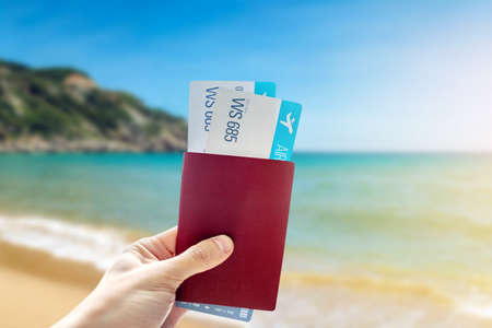 Hand holding a passport and two air tickets on a blue background of the sea. The concept of travel and vacation in beautiful exotic places Reklamní fotografie