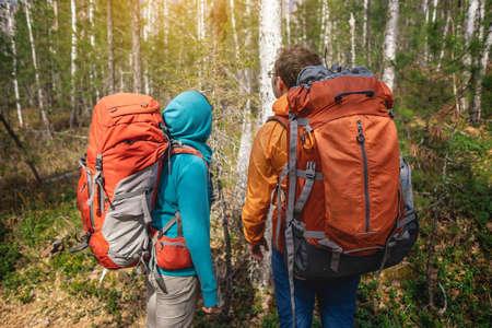後ろから日没の中をバックパックを持って歩く森のハイカーのグループ。冒険旅行、観光、ハイキング、人々の友情の概念。スポーツイベント