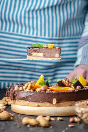 Pastry chef in hand holding a piece of chocolate cake with orange, mint leaves, peanuts and nuts. Healthy raw gluten-free and milk-and flour-free desserts for vegan food
