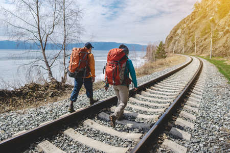 Tourists Hiking with orange backpacks are on the old railway at the foot of the mountain. Travel to lake Baikal, Russia