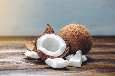 Open coconut with white pulp on wooden background. Organic healthy dietary vegan product widely used in cosmetics