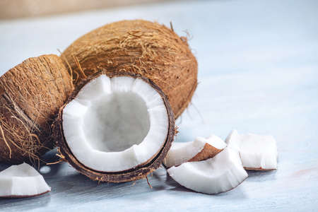 Open coconut with white pulp on blue wooden background. Organic healthy dietary vegan product widely used in cosmetics