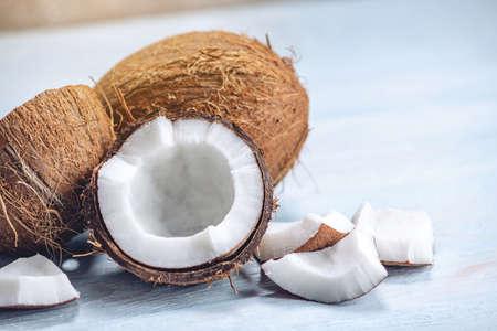 Otwórz kokos z białą miazgą na niebieskim tle drewnianych. Ekologiczny zdrowy dietetyczny wegański produkt szeroko stosowany w kosmetyce