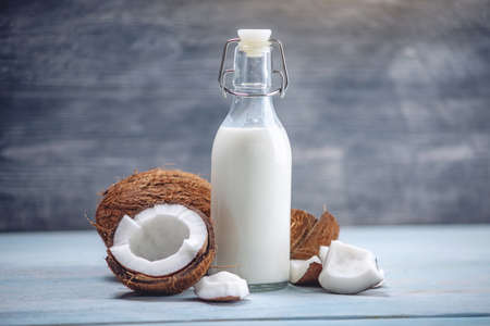 Coconut milk in a bottle in a composition with an open coconut with white flesh on a blue wooden background. Organic healthy dietary vegan product used in cosmetology and Spa