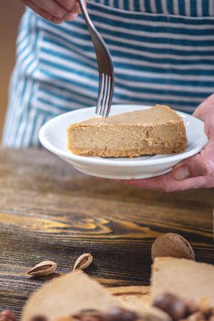 A piece of raw nutty cake decorated with walnut, almond, macadamia and hazelnut on a dark wooden background. Healthy fresh summer vegan dessert. Gluten free and sugar free food
