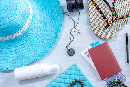 Travel holiday supplies: hat, sunglasses, flip flops, camera, passport and airline tickets on blue background. Concept of going on a trip to the sea on vacation. Top view. Flat lay Stockfoto