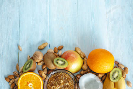 Healthy vegan raw foods on blue wooden background. Fruits and nuts with honey on the table. Natural organic sweet dessert. Place for text