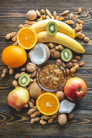 Healthy vegan raw foods on dark wooden background. Fruits and nuts with honey on the table pile. Natural organic sweet dessert