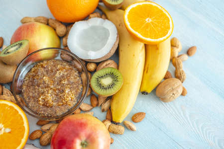 Healthy vegan raw foods on blue wooden background. Fruits and nuts with honey on the table. Natural organic sweet dessert.
