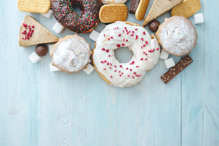 Harmful sweet foods on blue wooden background. Donuts, muffins, chocolates on the table pile. The concept of unhealthy diet and overweight. The view from the top. Place for text