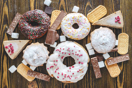 Harmful sweet foods on a dark wooden background. Donuts, muffins, chocolates on the table pile. The concept of unhealthy diet and overweight. Top view