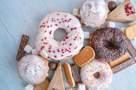 Harmful sweet foods on blue wooden background. Donuts, muffins, chocolates on the table pile. The concept of unhealthy diet and overweight. The view from the top