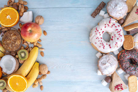 Unhealthy and healthy sweets on blue wooden background. Organic and dietary food and the problem of refusal from harmful desserts. Fruits and nuts vs donuts cupcakes and candy 写真素材