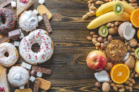 Unhealthy and healthy sweets on wooden background. Organic and dietary food and the problem of refusal from harmful desserts. Fruits and nuts vs donuts cupcakes and candy Reklamní fotografie