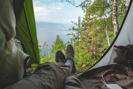 View from the tent on lake Baikal among the pine trees from the hill. The concept of tourism and recreation in the most beautiful places of the planet.