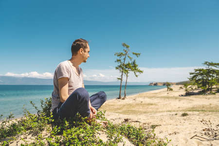 Man traveler relaxing on the beach of Olkhon island overlooking the water of the lake and the mountains and the blue sky Stok Fotoğraf