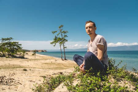 Man traveler relaxing on the beach of Olkhon island overlooking the water of the lake and the mountains and the blue sky Фото со стока