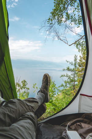 View from the tent on lake Baikal among the pine trees from the hill. Recreation in the beautiful places of the planet.