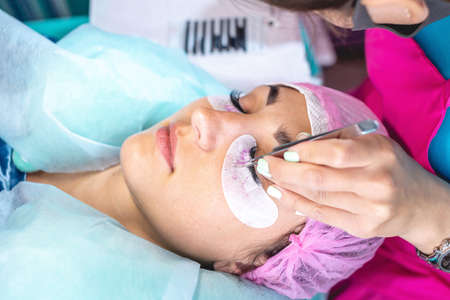 Woman master in the beauty salon work on eyelash extension to the client. Concept of profession in the field of beauty services