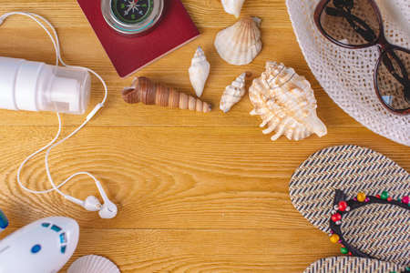 Accessories for a bright summer Sunny holiday in the resort. Items for travel to the sea laid out on a wooden table. Top view. Flat lay Stok Fotoğraf
