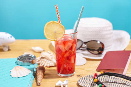 Glass of red lemonade drink with lemon and fruit and straw on the table. Accessories for summer Sunny holidays in the resort Stok Fotoğraf