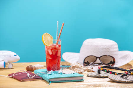 Glass of red lemonade drink with lemon and fruit and straw on the table. Concept of summer Sunny vacation at the resort.