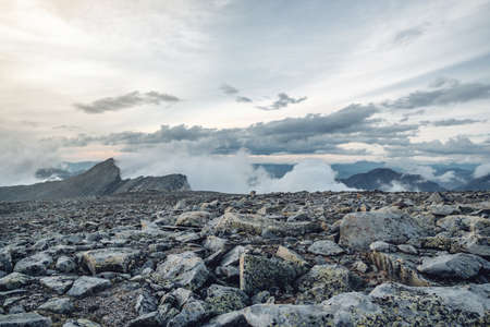 Beautiful view of the mountains from the peak. Landscape with clouds and stones at sunset. The concept of climbing and Hiking Banco de Imagens