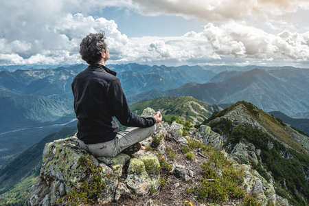 Man hiker sitting in a yoga pose at the peak of the mountain in the summer. Meditation after a long climb on a mountain background of cloudy sky in the evening